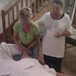 Lotta instruerar och hjälper alla att utföra massagegreppen effleurage, petrissage och friktioner